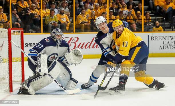Nick Bonino of the Nashville Predators battles against Tyler Myers and Connor Hellebuyck of the Winnipeg Jets in Game Two of the Western Conference...