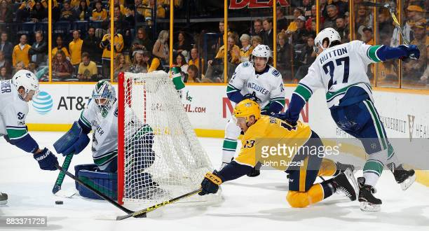 Nick Bonino of the Nashville Predators scores from behind the net against Anders Nilsson of the Vancouver Canucks during an NHL game at Bridgestone...