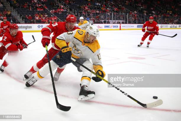 Nick Bonino of the Nashville Predators tries to control the puck in front of Adam Erne of the Detroit Red Wings during the third period at Little...