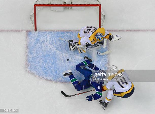 Nick Bonino of the Nashville Predators trips Elias Pettersson of the Vancouver Canucks on a breakaway resulting in a penalty shot during their NHL...