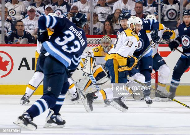 Nick Bonino of the Nashville Predators turns as he tries to block the shot off the point from Dustin Byfuglien of the Winnipeg Jets during first...