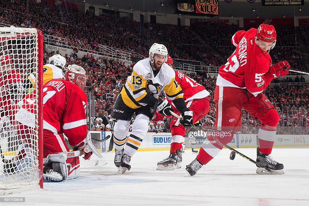 Nick Bonino #13 of the Pittsburgh Penguins battles for the puck with Alexei Marchenko #53 of the Detroit Red Wings in front of Jared Coreau #31 of the Wings during an NHL game at Joe Louis Arena on January 14, 2017 in Detroit, Michigan.