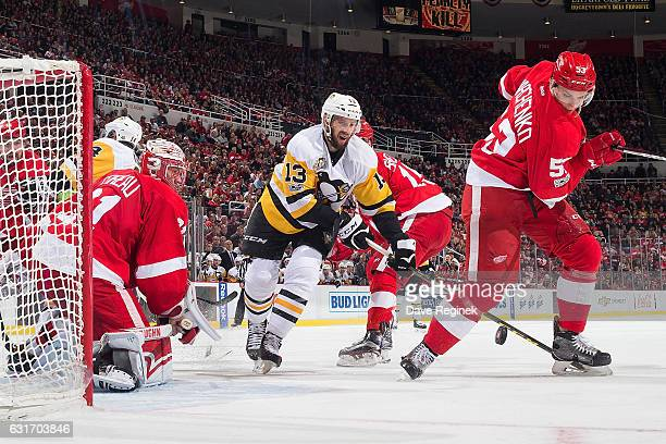 Nick Bonino of the Pittsburgh Penguins battles for the puck with Alexei Marchenko of the Detroit Red Wings in front of Jared Coreau of the Wings...