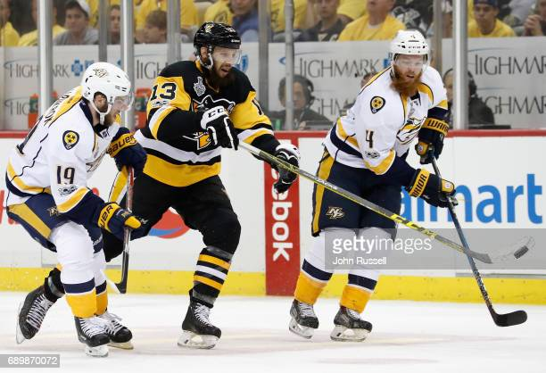 Nick Bonino of the Pittsburgh Penguins taps the puck away from Calle Jarnkrok and Ryan Ellis of the Nashville Predators during the first period of...
