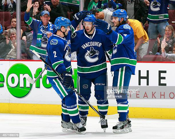 Nick Bonino of the Vancouver Canucks is congratulated by teammates Dan Hamhuis and Christopher Tanev after scoring during their NHL game against the...