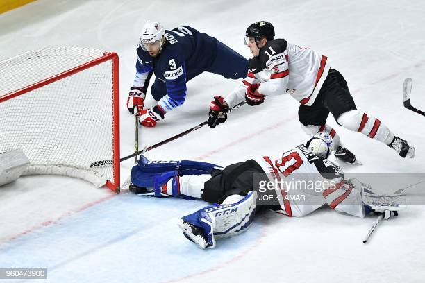 US Nick Bonino vies with Canada's goalkeeper Curtis McElhinney and Canada's JeanGabriel Pageau during the bronze medal match USA vs Canada of the...