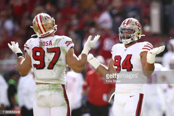 Nick Bosa and Solomon Thomas of the San Francisco 49ers react after sacking Kyle Allen of the Carolina Panthers during the second quarter at Levi's...