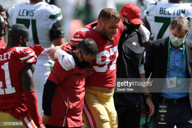 Nick Bosa of the San Francisco 49ers is helped off the field after an injury during the first half of the game against the New York Jets at MetLife...