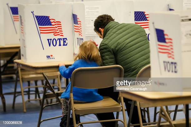 Nick Botto casts a ballot at Bedford High School with his 3 year old daughter Violet during the New Hampshire primary on February 11 2020 in Bedford...