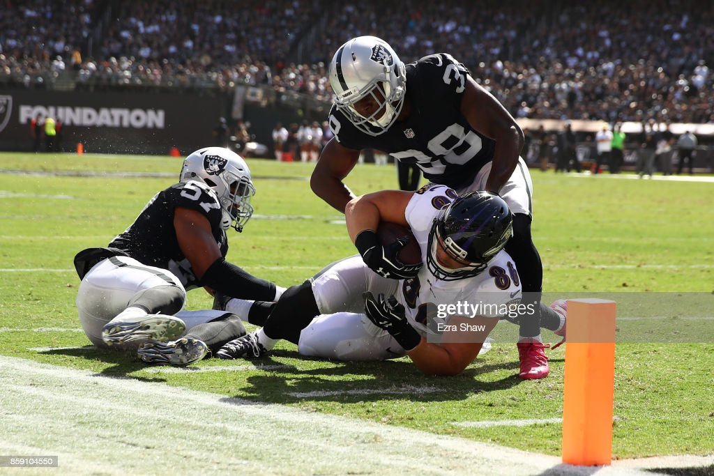 Nick Boyle #86 of the Baltimore Ravens is stopped short of the goal line by Cory James #57 of the Oakland Raiders during their NFL game at Oakland-Alameda County Coliseum on October 8, 2017 in Oakland, California.