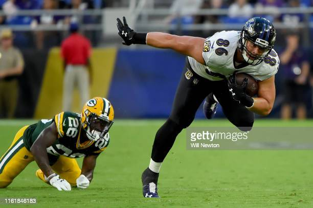 Nick Boyle of the Baltimore Ravens runs in front of Darnell Savage of the Green Bay Packers during the first half of a preseason game at MT Bank...