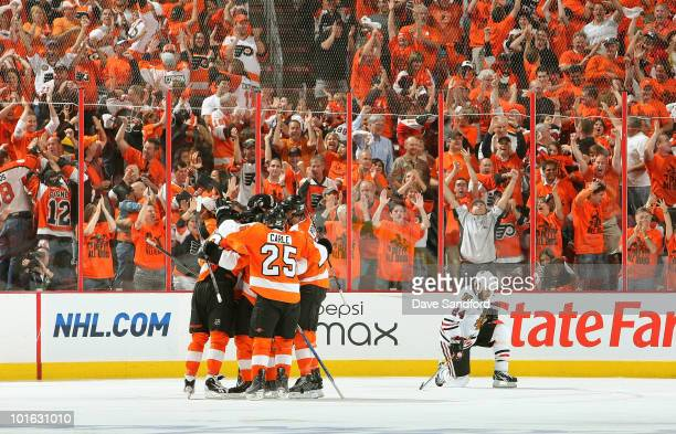 Nick Boynton of the Chicago Blackhawks kneels dejected as Ville Leino and Daniel Briere of the Philadelphia Flyers celebrate Leino's goal in the...