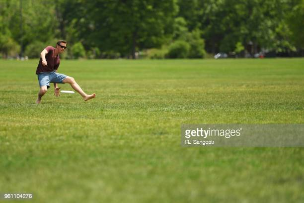 Nick Brown plays frisbee at Washington Park before thunderstorms move back into the area on May 21 2018 in Denver Colorado