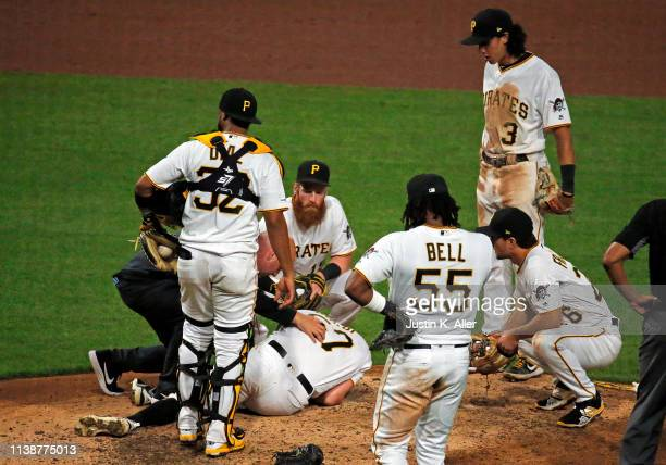 Nick Burdi of the Pittsburgh Pirates lays injured on the ground in the eighth inning against the Arizona Diamondbacks at PNC Park on April 22 2019 in...