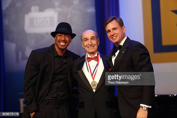 Nick Cannon and President CEO USO of Metropolitan New York Brian Whiting present an award onstage at the USO 75th Anniversary Armed Forces Gala Gold...
