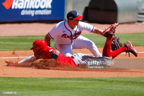 Nick Castellanos of the Cincinnati Reds is out at third with the tag of Austin Riley of the Atlanta Braves in the sixth inning of Game One of the...