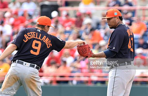 Nick Castellanos of the Detroit Tigers hands a baseball to Bruce Rondon during the Spring Training game against the Washington Nationals at Space...
