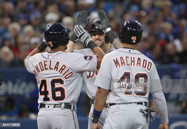 Nick Castellanos of the Detroit Tigers is congratulated by Jeimer Candelario and Dixon Machado after hitting a grand slam home run in the third...