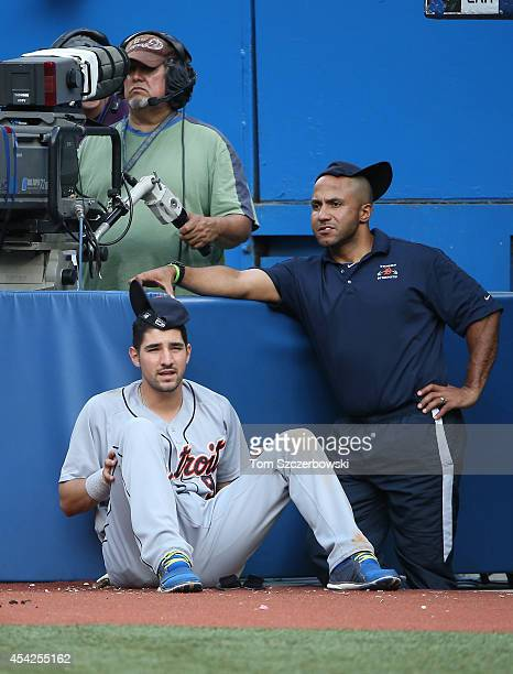 Nick Castellanos of the Detroit Tigers looks on beside strength and conditioning coach Javair Gillett from the top step of the dugout while wearing a...