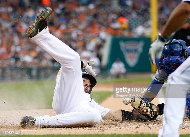 Nick Castellanos of the Detroit Tigers slides safely into home plate prior to a tag by Salvador Perez of the Kansas City Royals during the second...