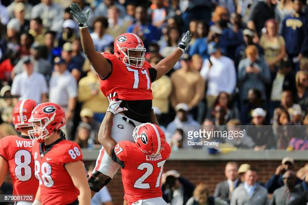 Nick Chubb celebrates a touchdown by lifting up Isaiah Wynn of the Georgia Bulldogs during the first half against the Georgia Tech Yellow Jackets at...