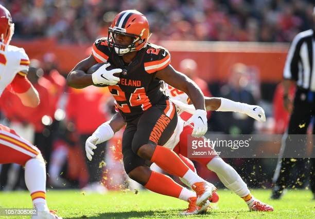 Nick Chubb of the Cleveland Browns carries the ball in front of Kendall Fuller of the Kansas City Chiefs during the second quarter at FirstEnergy...