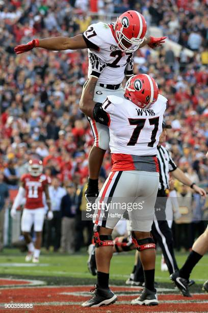 Nick Chubb of the Georgia Bulldogs and Isaiah Wynn of the Georgia Bulldogs celebrate after a 50 yard touchdown in the 2018 College Football Playoff...