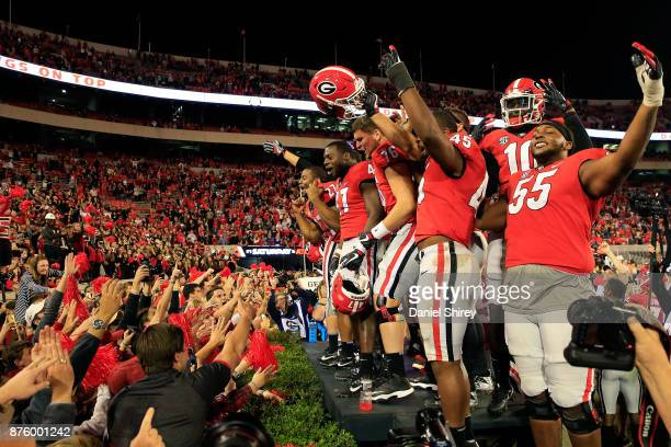 Nick Chubb of the Georgia Bulldogs and teammates celebrate with fans after beating the Kentucky Wildcats at Sanford Stadium on November 18 2017 in...