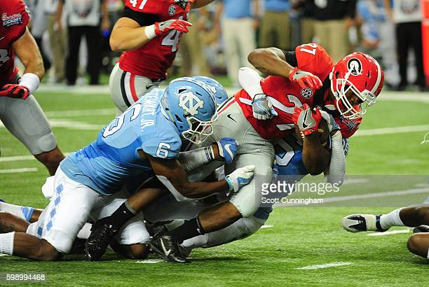 Nick Chubb of the Georgia Bulldogs carries defenders M J Stewart Naziar Jones and Donnie Miles of the North Carolina Tar Heels at the Georgia Dome on...