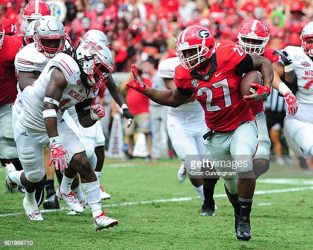 Nick Chubb of the Georgia Bulldogs gets set to stiffarm Ahmani Martin of the Nicholls Colonels at Sanford Stadium on September 10 2016 in Athens...