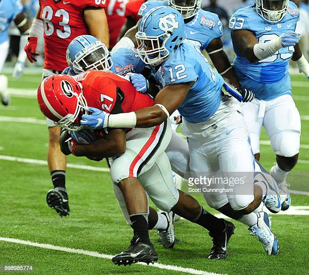 Nick Chubb of the Georgia Bulldogs is brought down by a facemask by Timmon Fox of the North Carolina Tar Heels at the Georgia Dome on September 3...