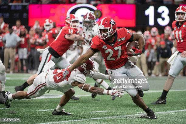 Nick Chubb of the Georgia Bulldogs is tackled by Anthony Averett of the Alabama Crimson Tide during the College Football Playoff National...