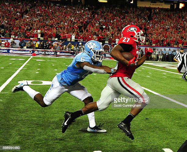 Nick Chubb of the Georgia Bulldogs runs for a 55 yard touchdown against M J Stewart of the North Carolina Tar Heels at the Georgia Dome on September...