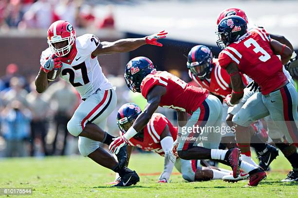 Nick Chubb of the Georgia Bulldogs runs the ball and is pursued by the defense of the Mississippi Rebels at VaughtHemingway Stadium on September 24...