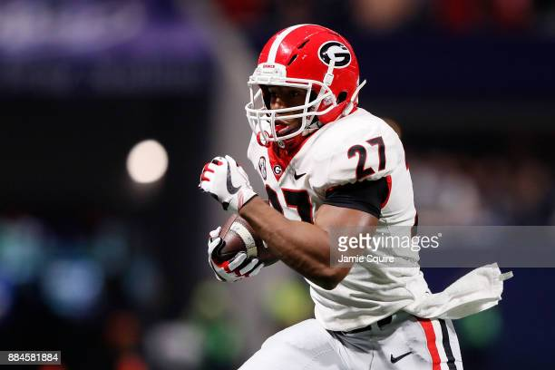 Nick Chubb of the Georgia Bulldogs runs the ball during the first half against the Auburn Tigers in the SEC Championship at MercedesBenz Stadium on...