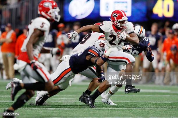 Nick Chubb of the Georgia Bulldogs runs the ball during the second half against the Auburn Tigers in the SEC Championship at MercedesBenz Stadium on...