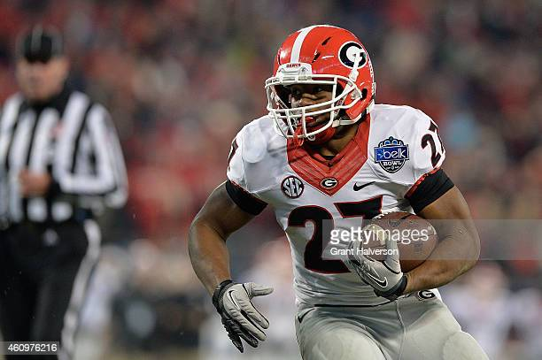 Nick Chubb of the Georgia Bulldogs rus against the Louisville Cardinals during the Belk Bowl at Bank of America Stadium on December 30 2014 in...