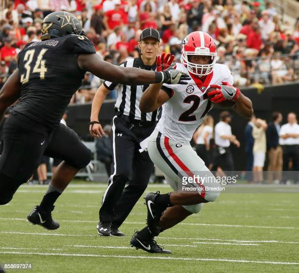 Nick Chubb of the Georgia Bulldogs rushes against Dare Odeyingbo of the Vanderbilt Commodores during the first half at Vanderbilt Stadium on October...