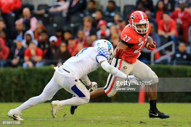 Nick Chubb of the Georgia Bulldogs stiff arms Mike Edwards of the Kentucky Wildcats during the first half at Sanford Stadium on November 18 2017 in...