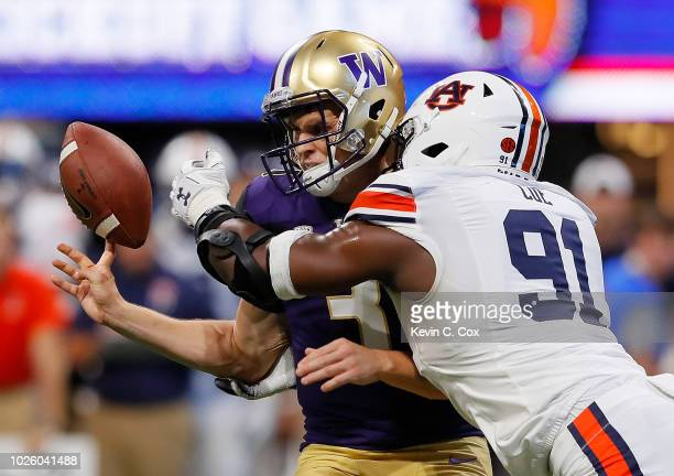 Nick Coe of the Auburn Tigers forces a fumble as he knocks the ball from the hands of Jake Browning of the Washington Huskies at MercedesBenz Stadium...