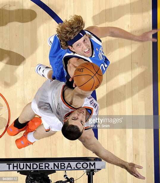 Nick Collison of the Oklahoma City Thunder goes for a rebound against Dirk Nowitzki of the Dallas Mavericks during the game at the Ford Center on...