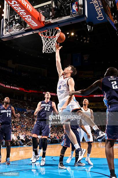 Nick Collison of the Oklahoma City Thunder shoots a layup against DeSagana Diop of the Charlotte Bobcats on November 26 2012 at the Chesapeake Energy...