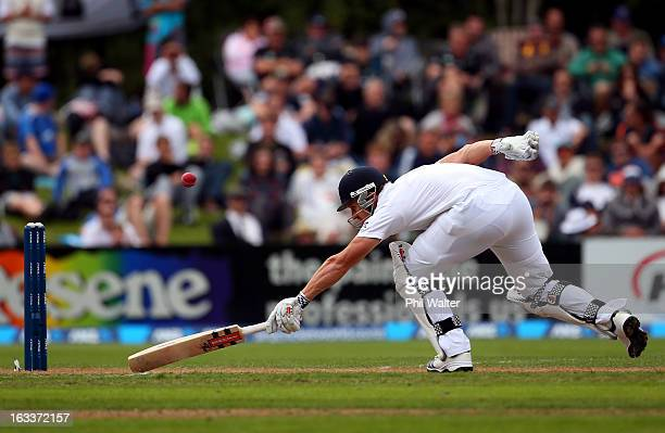 Nick Compton of England stretches to make his ground during day four of the First Test match between New Zealand and England at University Oval on...