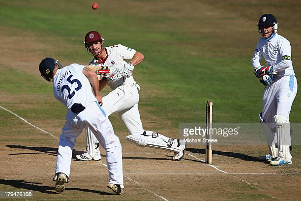 Nick Compton of Somerset sees his legside shot bounce off Richard Johnson of Derbyshire as wicketkeeper Thomas Poynton looks on during day two of the...
