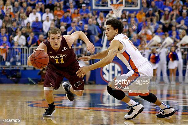 Nick Coppola of the Louisiana Monroe Warhawks drives past Chris Chiozza of the Florida Gators during the first half of the game at Stephen C...