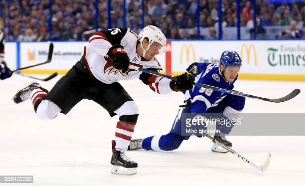 Nick Cousins of the Arizona Coyotes and Mikhail Sergachev of the Tampa Bay Lightning fight for the puck during a game at Amalie Arena on March 26...