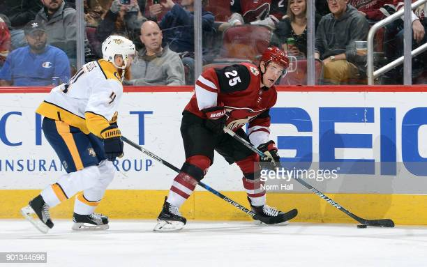 Nick Cousins of the Arizona Coyotes skates with the puck ahead of Ryan Ellis of the Nashville Predators during the first period at Gila River Arena...