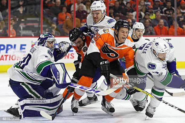 Nick Cousins of the Philadelphia Flyers is bodychecked by Nikita Tryamkin of the Vancouver Canucks during the second period at Wells Fargo Center on...