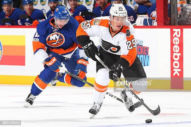 Nick Cousins of the Philadelphia Flyers plays the puck against Alan Quine of the New York Islanders at the Barclays Center on January 22 2017 in...