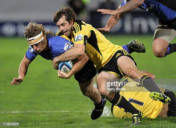 Nick Cummins of the Force is tackled by Conrad Smith of the Hurricanes during the round 15 Super Rugby match between the Hurricanes and the Western...